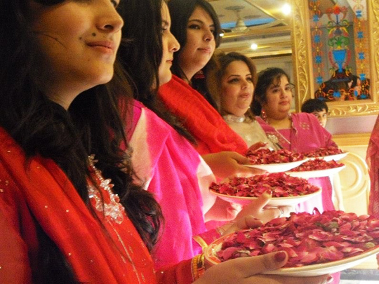 Girls waiting for the groom and his guests to shower them with rose petals