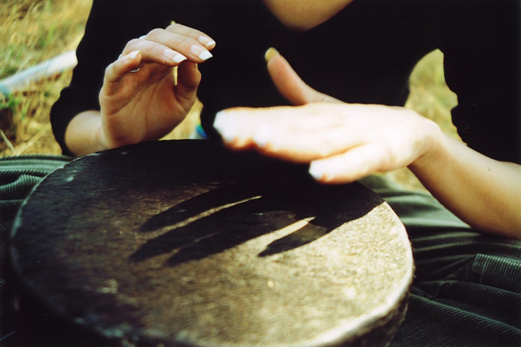 A woman plays with the variations of sound produced by her drum.